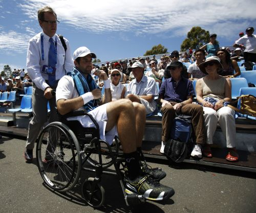 Brian Baker of the U.S. is wheeled from the court after retiring injured from his men's singles match against compatriot Sam Querrey