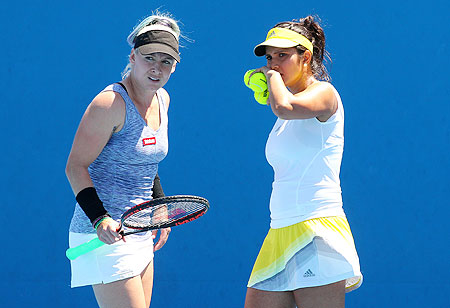 Bethanie Mattek-Sands (left) talks tactics with doubles partner Sania Mirza on Wednesday