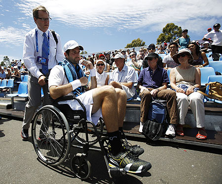 Brian Baker of the US is wheeled off the court after retiring injured from his men's singles match against compatriot Sam Querrey at the Australian Open on Wednesday