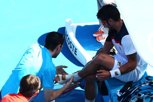 Janko Tipsarevic of Serbia receives medical attention in his fourth round match against Nicolas Almagro of Spain during day seven of the Australian Open