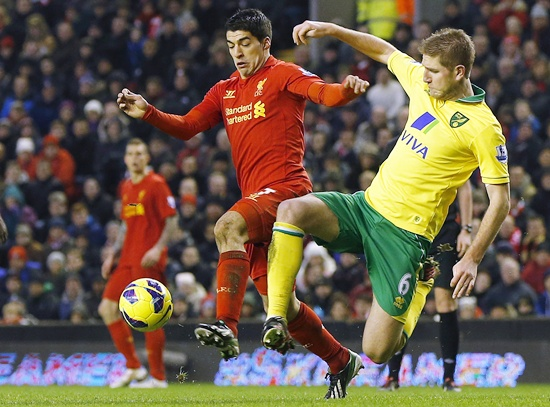 Liverpool's Luis Suarez (left) challenges Norwich City's Michael Turner