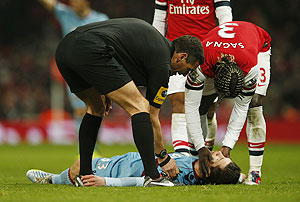 West Ham's Daniel Potts is checked by Arsenal's Bacary Sagna (R) and referee Andre Marriner after he was injured during their match on Wednesday