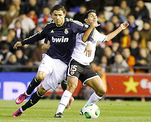 Real Madrid's Cristiano Ronaldo (left) and Valencia's Joanathan Viera vie for the ball during their King's Cup quarter-final second leg match at the Mestalla stadium in Valencia, on Wednesday