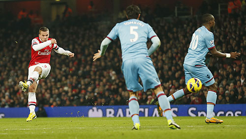 Arsenal's Lukas Podolski (left) scores past West Ham's James Tomkins and Guy Demel (right)