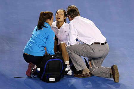 Na Li of China receives medical attention after falling for the second time during her women's final match against Victoria Azarenka