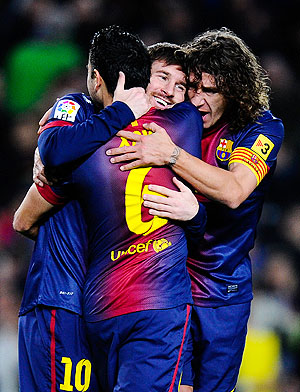 Barcelona'S Lionel Messi (centre) celebrates with teammates Xavi Hernandez (left) and Carles Puyol after scoring the opening goal against Osasuna during their La Liga match on January Sunday