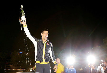 Novak Djokovic celebrates with a bottle of champagne after winning the final against Andy Murray on Sunday