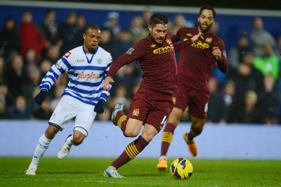 Javi Garcia of Manchester City clears the ball as Loic Remy of QPR closes in during the Premier League match at Loftus Road