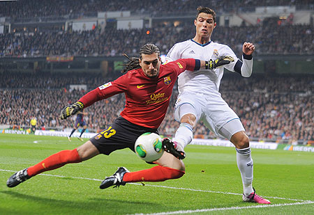 Cristiano Ronaldo (right) battles for the ball with Jose Manuel Pinto of Barcelona