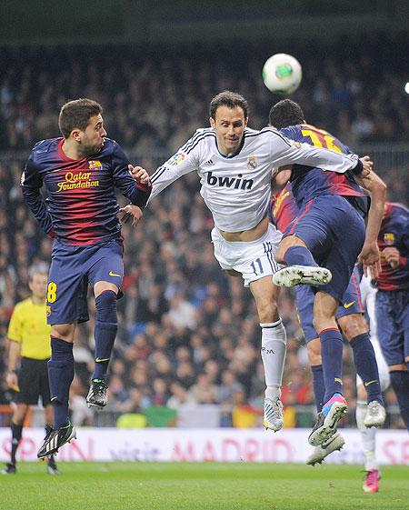 Real Madrid's Ricardo Carvalho (right) goes for a high ball against Jordi Alba of Barcelona