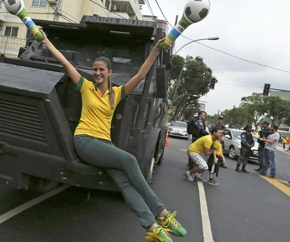 A Brazilian soccer fan poses on the riot police armoured car