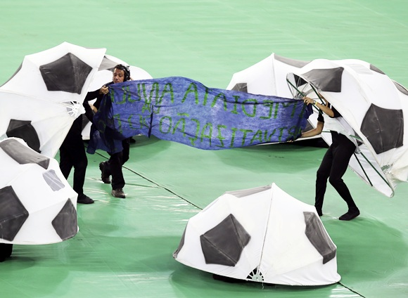 Two dancers unveil a banner in protest against the privatization of the Maracana stadium