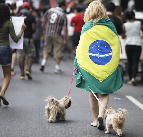 A woman walks her dogs during a protest on the streets near the Maracana stadium