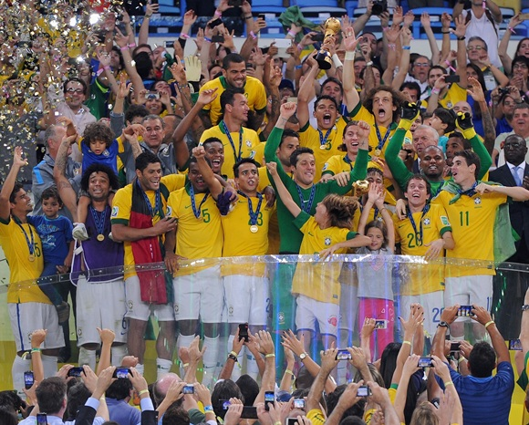 The Brazil players celebrate with the trophy