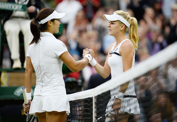 Agnieszka Radwanska of Poland shakes hands at the net with Na Li of China after their quarter-final