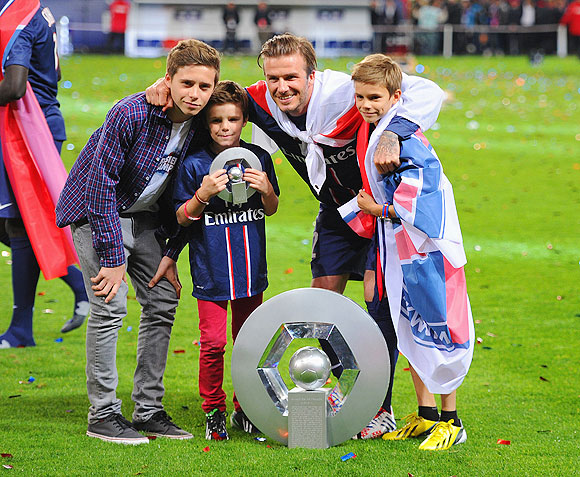 David Beckham poses wih the Ligue 1 trophy and his sons Brooklyn, Romeo and Cruz