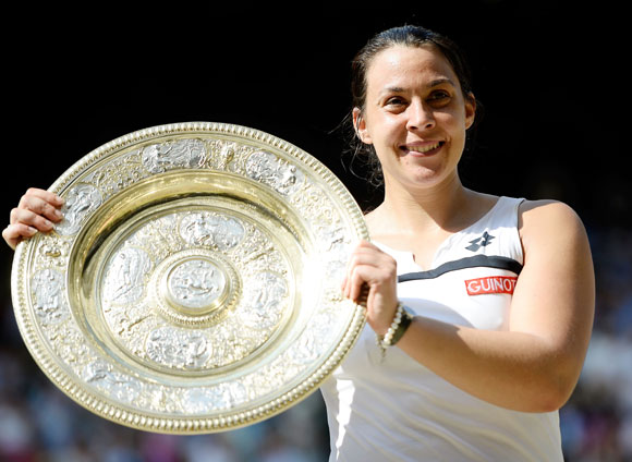 Marion Bartoli of France poses with the Venus Rosewater Dish trophy after her victory against Sabine Li