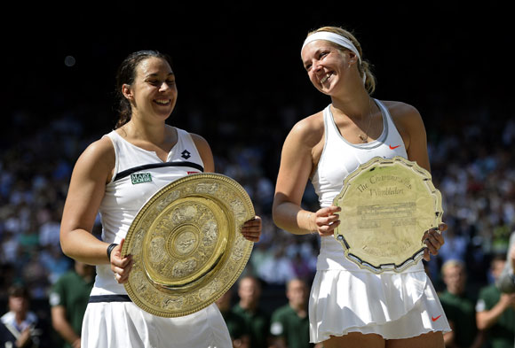 Marion Bartoli of France poses with the Venus Rosewater Dish trophy next to Sabine Lisicki of Germany and her runner-up trophy after the final