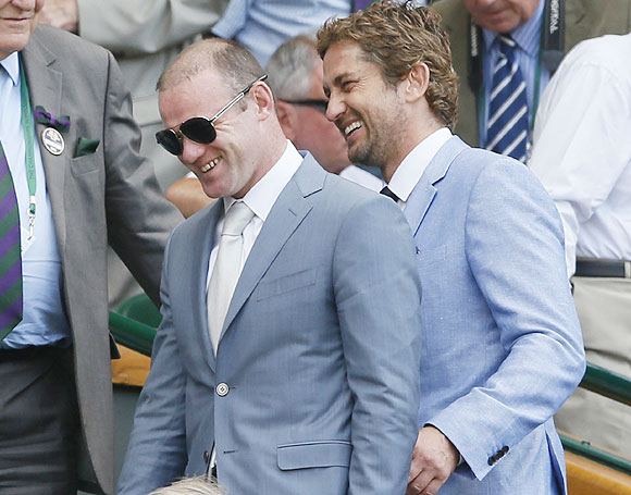 Footballer Wayne Rooney (left) and Hollywood actor Gerard Butler walk on Centre Court for the men's Wimbledon final on Sunday