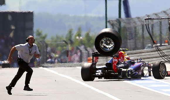 An unidentified FIA official runs over to the pits as a lost rear tyre of Red Bull Formula One driver Mark Webber of Australia bounces through the pit lane during the German F1 Grand Prix on Sunday