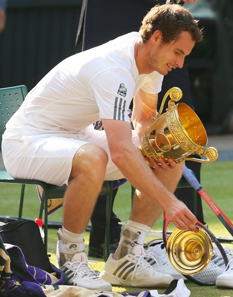 Andy Murray of Great Britain drops the lid of the Gentlemen's Singles Trophy