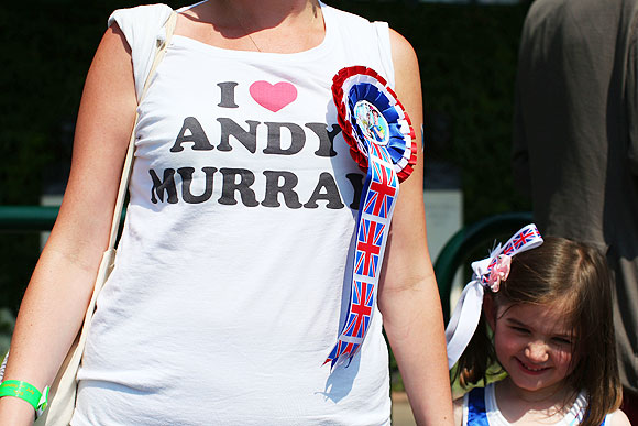 A tennis fan wears a t-shirt and rosette in support of Andy Murray