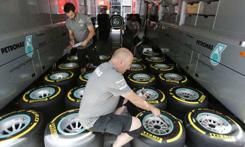 A Mercedes Formula One team technician checks the air pressure in the new Pirelli tyres