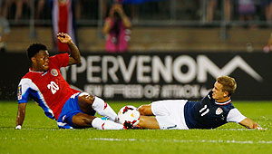 Rodney Wallace of Costa Rica (left) and Stuart Holden of the United States slide tackle as they vie for possession during the CONCACAF Gold Cup match at Rentschler Field in East Hartford, Connecticut on Tuesday