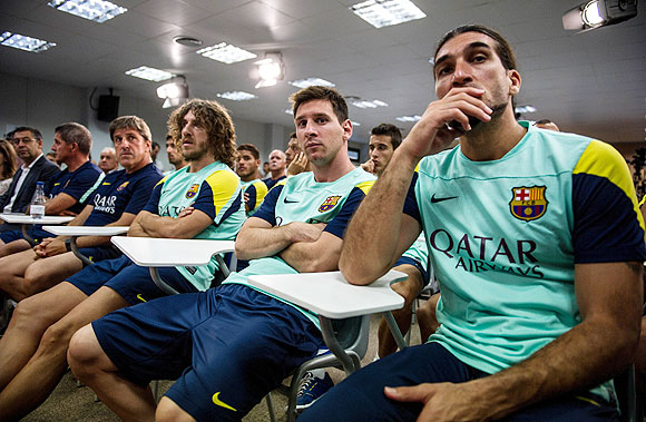 Assistant coach, Jordi Roura, Carles Puyol, Lionel Messi and Jose Manuel Pinto of FC Barcelona look on during a press conference by club President Sandro Rosell, announcing the news of Tito Vilanova's resignation at the Sant Joan Despi Sports Complex on Friday
