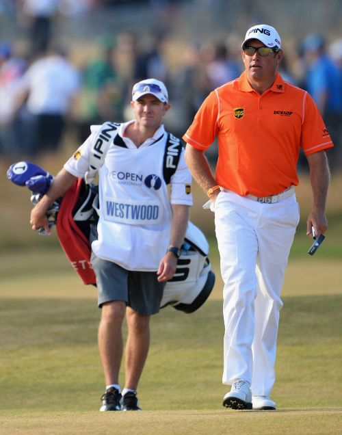 Lee Westwood of England walks up the 18th fairway with his caddie Michael Kerr