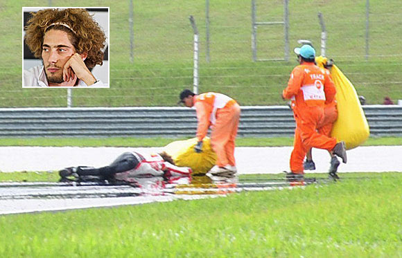 Honda MotoGP's Marco Simoncelli of Italy lies on the ground after a crash during the Malaysian Grand Prix in Sepang