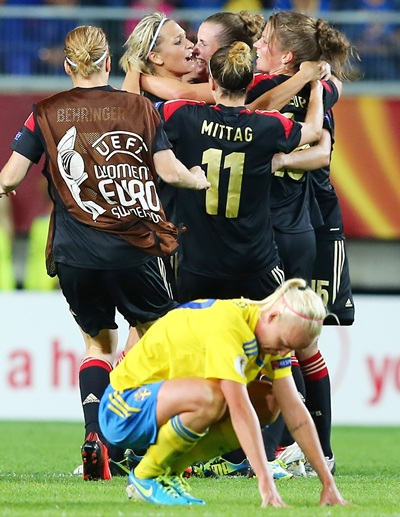 Lena Goessling (centre) of Germany celebrate with her teammates while Caroline Seger of Sweden looks dejected