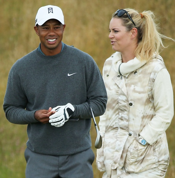 Tiger Woods of the United States smiles alongside skier Lindsey Vonn