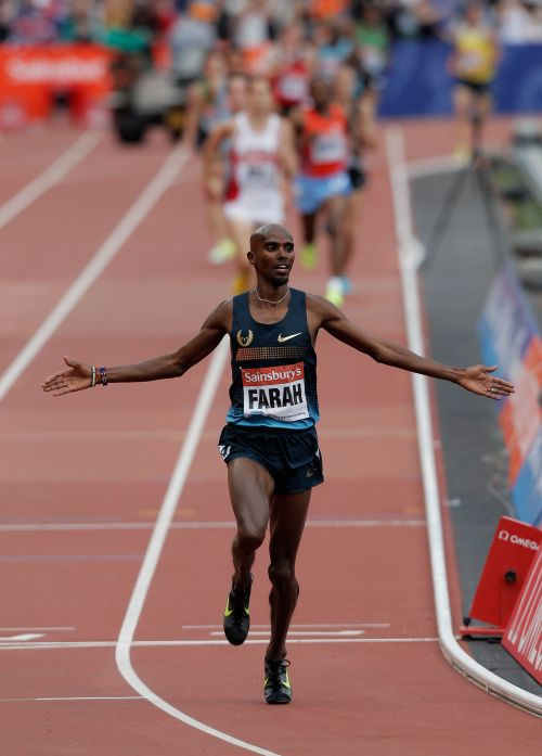 Mo Farah of Great Britain celebrates as he crosses the line in first place in the Men's 3000m duri