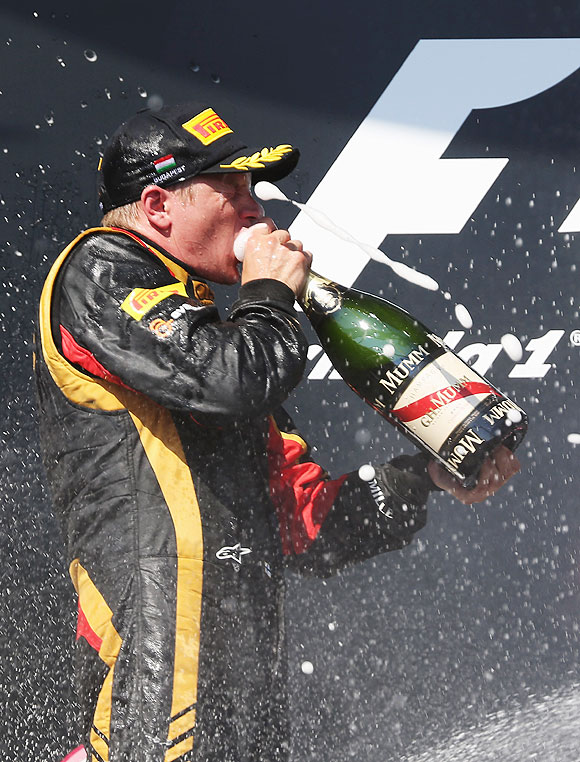 Kimi Raikkonen of Finland and Lotus celebrates on the podium after finishing second during the Hungarian Formula One Grand Prix at Hungaroring in Budapest, Hungary, on Sunday
