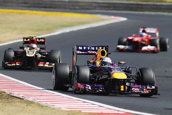 Sebastian Vettel of Germany and Infiniti Red Bull Racing leads from Romain Grosjean of France and Lotus during the Hungarian Formula One Grand Prix at Hungaroring in Budapest, Hungary, on Sunday