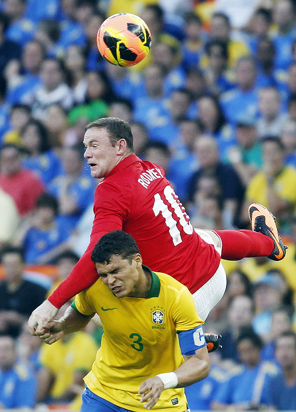 Brazil's Thiago (bottom) fights for the ball with England's Wayne Rooney during their international friendly at the Maracana Stadium in Rio de Janeiro on Sunday