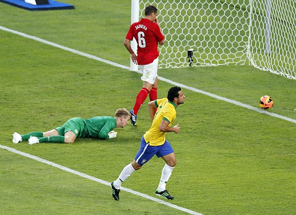 Brazil's Fred celebrates after shooting past England's goalkeeper Joe Hart and Phil Jagielka (top)