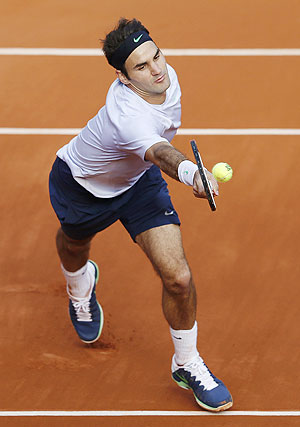 Roger Federer hits a return against Gilles Simon during the French Open at Roland Garros on Sunday
