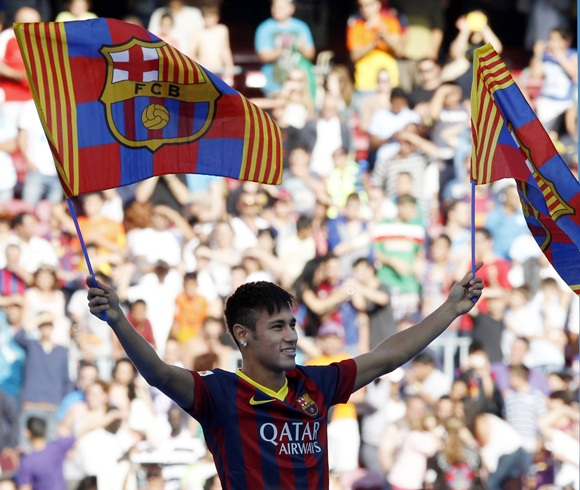 Brazilian soccer player Neymar waves Barcelona's flags