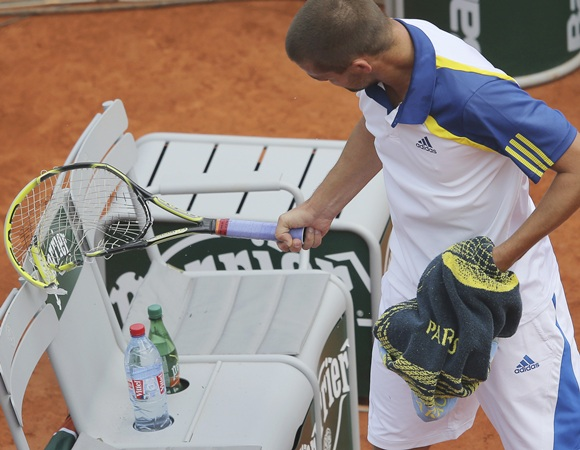 Mikhail Youzhny of Russia looks at his broken racket