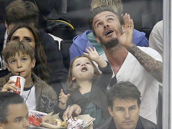David Beckham sits behind actor Tom Cruise with his daughter Harper, 3, sons and wife Victoria