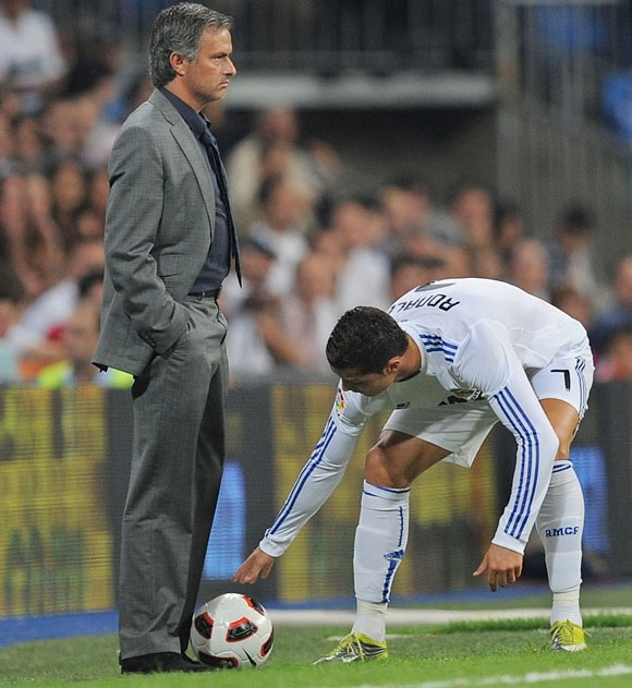 Cristiano Ronaldo of Ral Madrid picks up the ball at the feet of Real manager Jose Mourinho