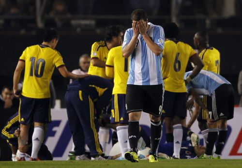 Argentina's Gonzalo Higuain (C) covers his face after being expelled by referee Marlon Escalante (not seen) of Venezuela during their 2014 World Cup qualifying soccer match against Colombia in Buenos Aires