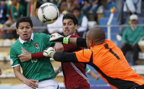 Venezuela's goalkeeper Renny Vega (R) deflects the ball away from Bolivia's Carlos Saucedo (L) as Venezuela's Gabriel Cichero watches during their 2014 World Cup qualifying soccer match in La Paz
