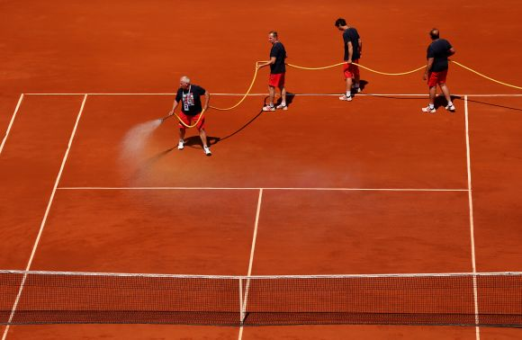Court attendants water the clay on Court Philippe Chatrier during a break in the men's singles semi-final match between Novak Djokovic of Serbia and Rafael Nadal of Spain