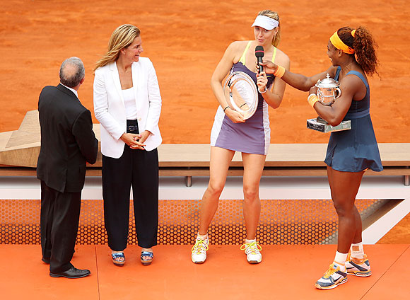 Serena Williams (right) hands runner-up Maria Sharapova the microphone as Francesco Ricci Bitti (left) and Arantxa Sanchez Vicario (2nd from left) look on