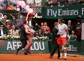 Rafael Nadal of Spain looks on as security guards restrain a protester after he lit a flare and ran on court during the men's singles final on Sunday