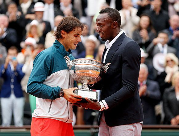 Rafael Nadal of Spain receives the Coupe des Mousquetaires trophy from Usian Bolt after winning beating David Ferrer to win the men's singles final on Sunday