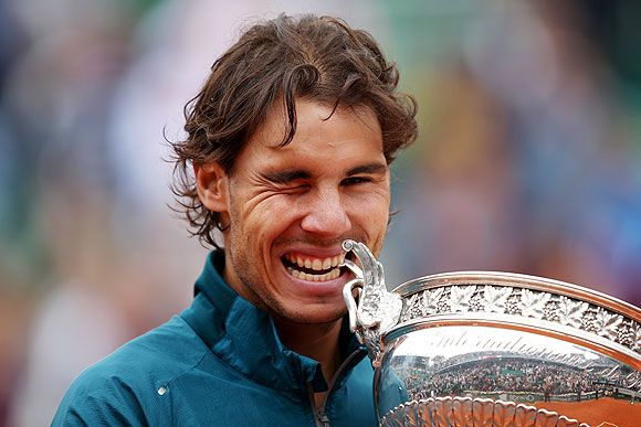Rafael Nadal of Spain winks celebrates with the Coupe des Mousquetaires trophy after winning the French Open on Sunday